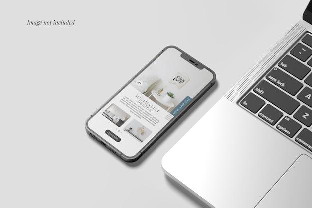 Smartphonemodel naast de laptop Premium Psd