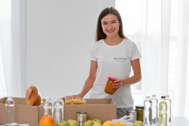 Smiley vrouwelijke vrijwilliger die voedsel voorbereidt voor donatie
