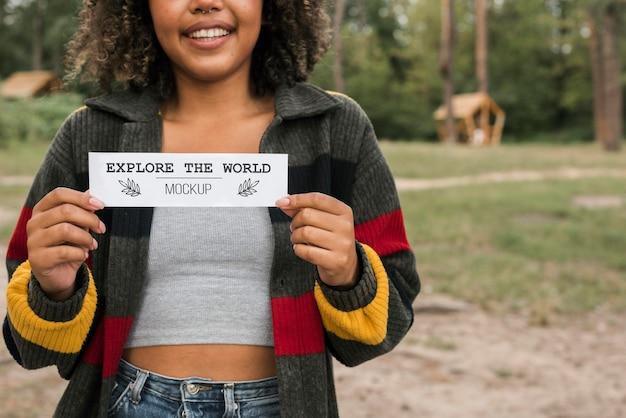 Smileyvrouw met een stuk papier tijdens het kamperen