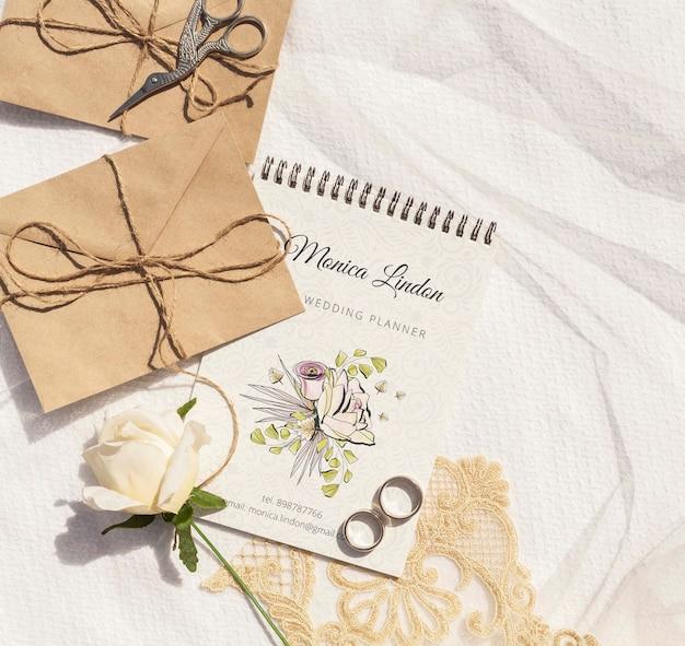 Sobres de papel marrón con anillos de boda y rosa.