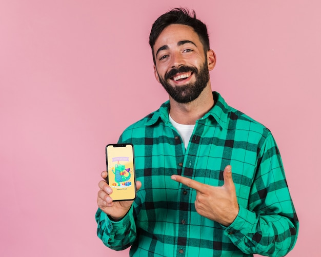Sonriente joven dedo acusador en teléfono celular simulacro