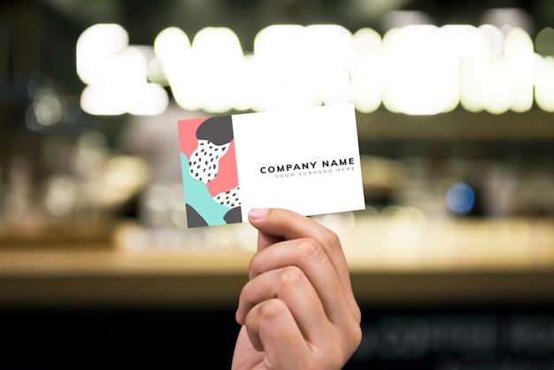 Sosteniendo una maqueta de tarjeta de visita