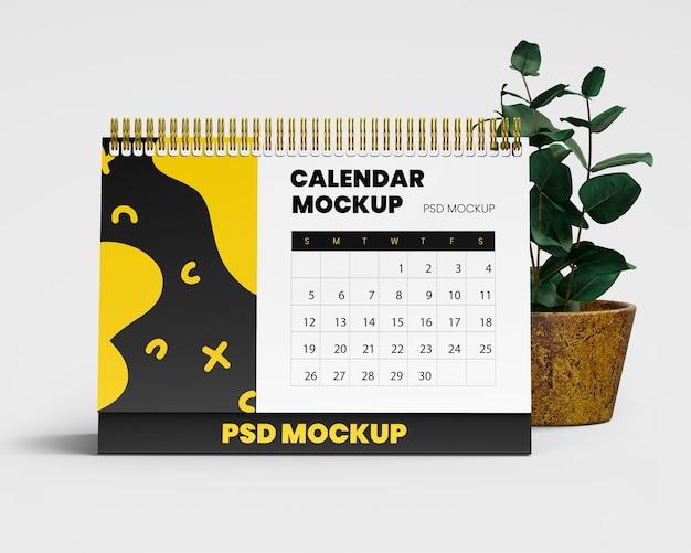 Spiraalvormige bureaukalender mockup met plant