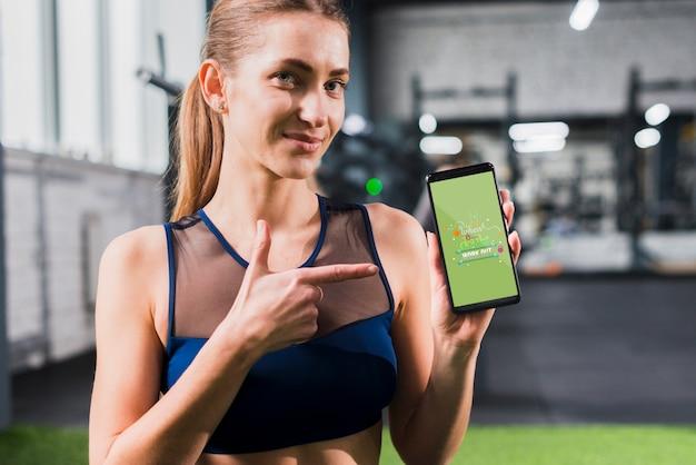 Sportieve vrouw die op smartphonemodel richt