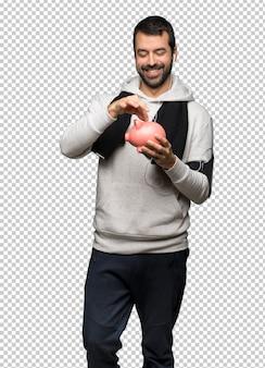 Sportman die een spaarvarken neemt en gelukkig omdat het vol is