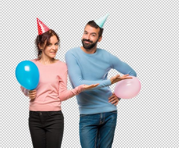 Stel met ballonnen en verjaardagshoeden een idee presenteren terwijl u op zoek naar glimlachen