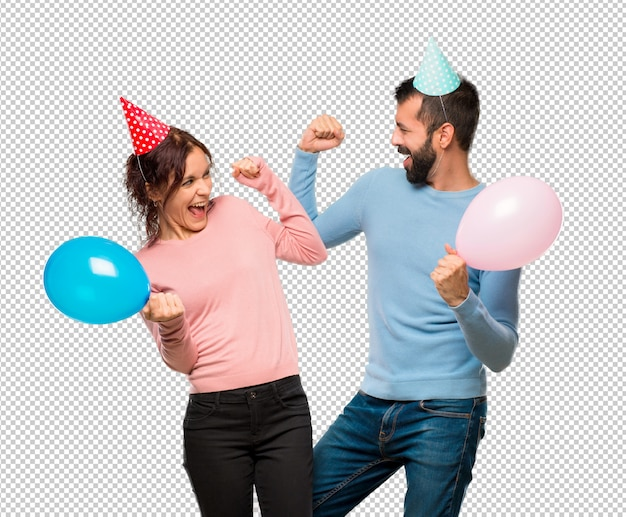Stel met ballons en verjaardagshoeden viert een overwinning in winnaarpositie
