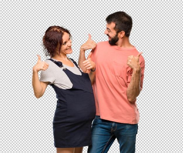 Stel met zwangere vrouw die een duim op gebaar geeft en glimlacht omdat succes heeft gehad