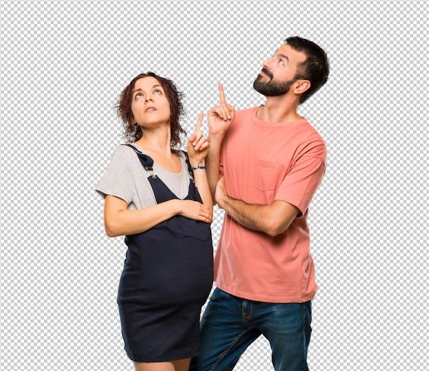Stel met zwangere vrouw die met de vinger een groot idee richt en omhoog kijkt