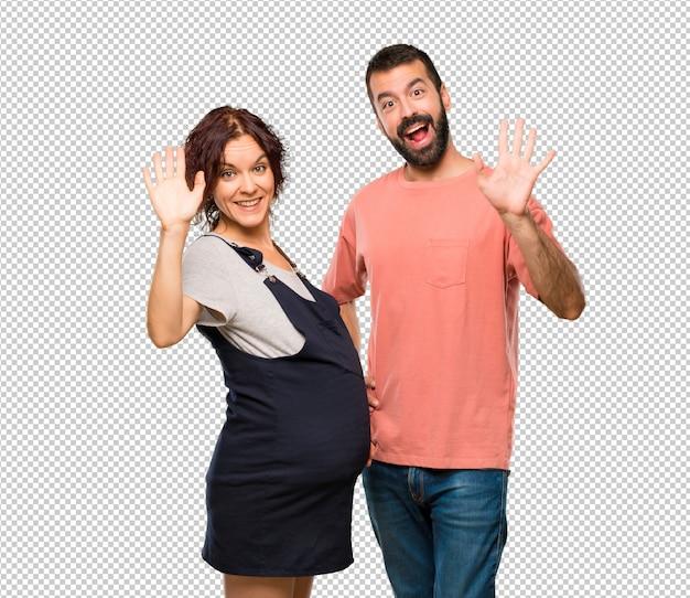 Stel met zwangere vrouw die met hand met gelukkige uitdrukking groeten