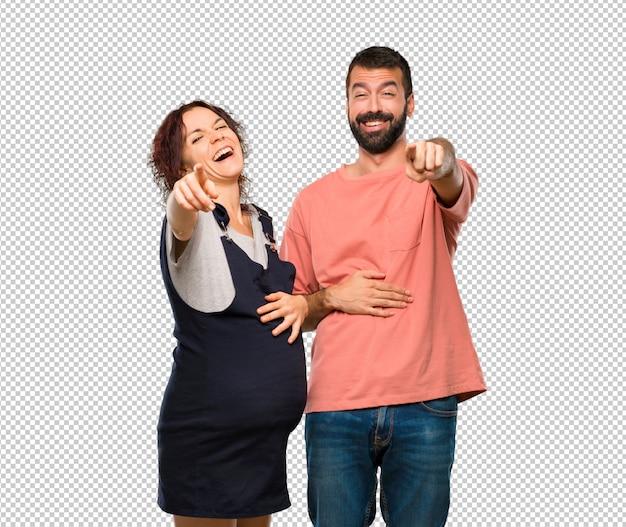 Stel met zwangere vrouw met een vinger wijzen op iemand en veel lachen