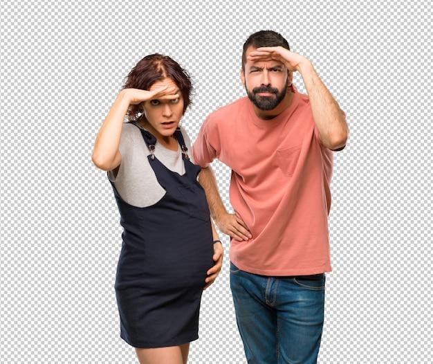 Stel met zwangere vrouw op zoek ver weg met de hand om iets te zoeken