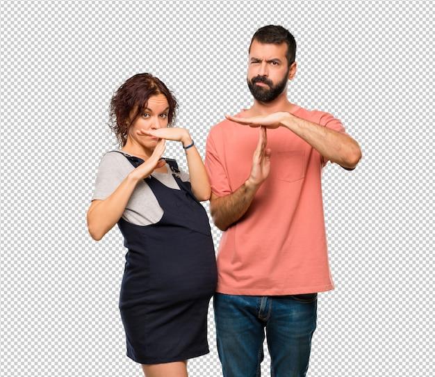Stel met zwangere vrouw stop gebaar maken met haar hand om een daad te stoppen