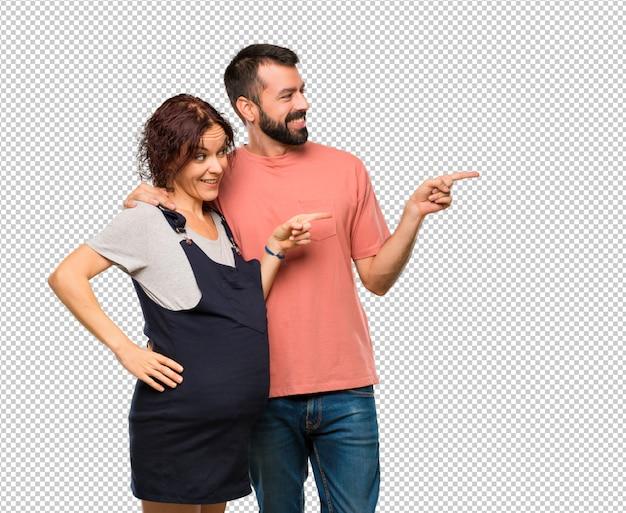Stel met zwangere vrouw wijzende vinger aan de kant en de presentatie van een product tijdens het glimlachen