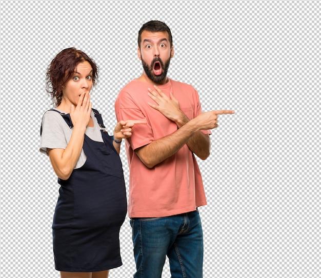 Stel met zwangere vrouw wijzende vinger aan de kant met een verbaasd gezicht