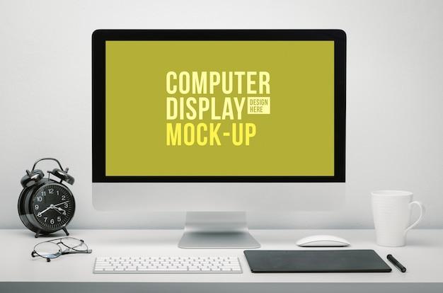 Stijlvolle werkruimte met een leeg computerscherm voor mockup op een bureau met toetsenbord, muis, kopje koffie, klok, bril en pentablet