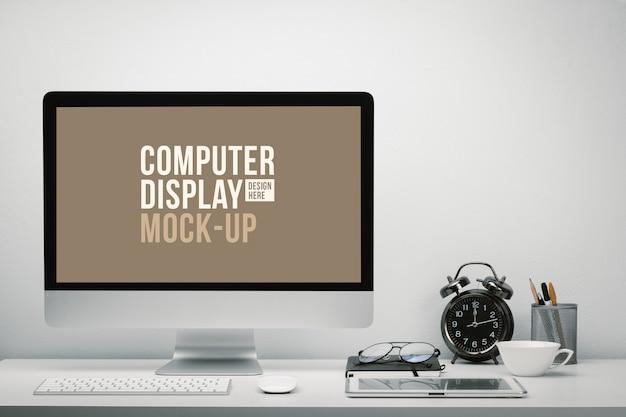 Stijlvolle werkruimte met leeg computerscherm en tablet voor mockup op bureau met toetsenbord, muis, klok, bril en briefpapier