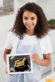 Struttura della tenuta della giovane donna con il messaggio dell'alimento