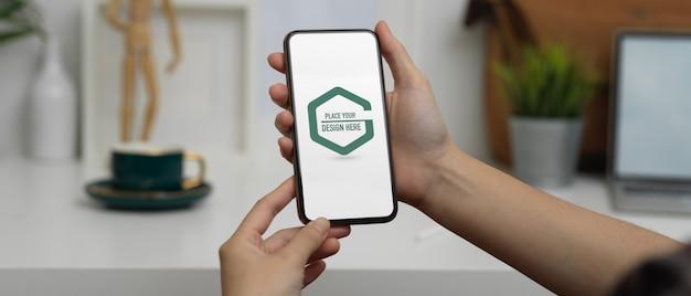 Studentenhanden die mockup-smartphone op kantoor gebruiken