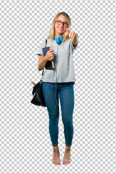 Studentenmeisje met duimen op gebaar geven en glimlachen die omdat iets goeds is gebeurd