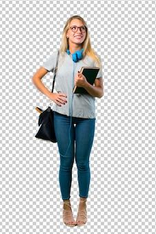 Studentenmeisje met glazen die met wapens bij heup en het lachen stellen