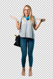 Studentenmeisje met glazen met verrassing en geschokte gelaatsuitdrukking. mond open omdat niet verwacht wat er is gebeurd