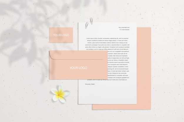 Summer blank branding mockup con biglietti da visita in corallo, buste su muro chiaro con fiori e ombre. lo smart layer di psd può muoversi. stazionario