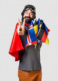 Super-herói com um monte de bandeiras, fazendo o gesto de vitória