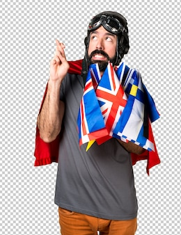 Superhéroe con muchas banderas con los dedos cruzándose.
