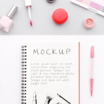 Surtido de cosméticos de maquillaje de vista superior con maqueta de bloc de notas