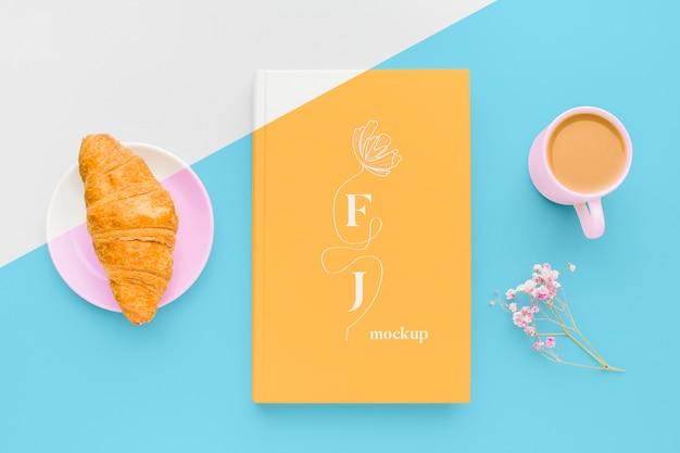 Surtido de maquetas de portadas de libros con taza de café y croissant