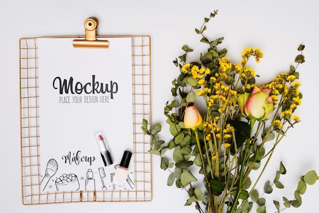 Surtido de vista superior de maqueta de maquillaje y flores