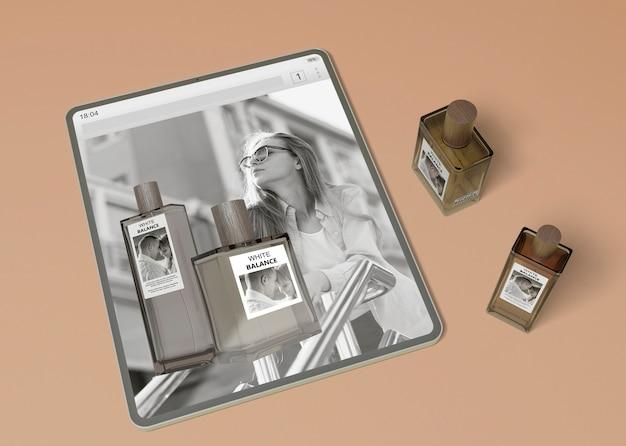 Tablet con sito web e bottiglie di profumo