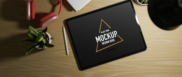 Tablet leeg scherm op werkruimte met rode koptelefoon kamerplant en licht van tafellamp