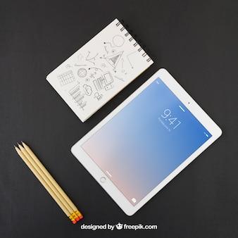Tablet, matite e taccuino con disegno