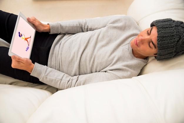 Tablet modello con l'uomo agghiacciante sul divano