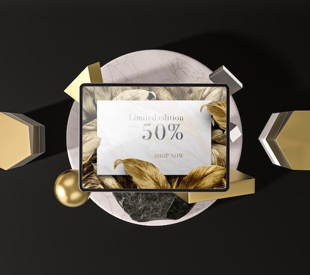 Tableta digital con vista superior de hojas doradas