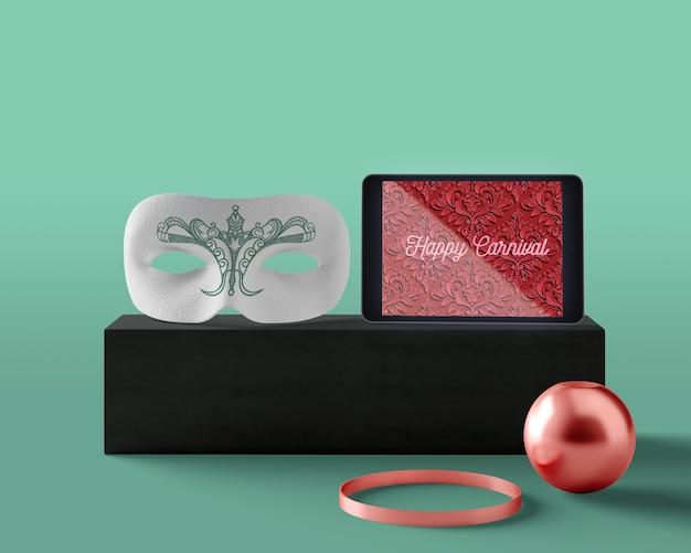 Tableta con diseño de carnaval al lado de la máscara
