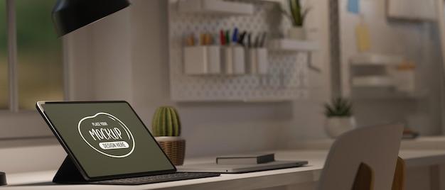 Tableta en el escritorio con poca luz de la lámpara de mesa con espacio de trabajo moderno diseñado en blanco y espacio de copia