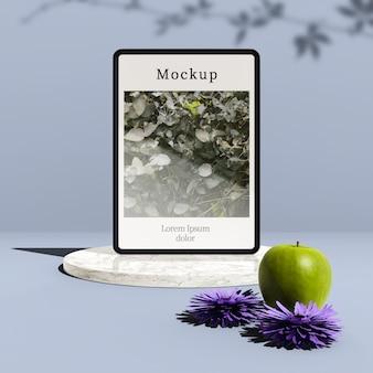 Tableta con flores y manzana