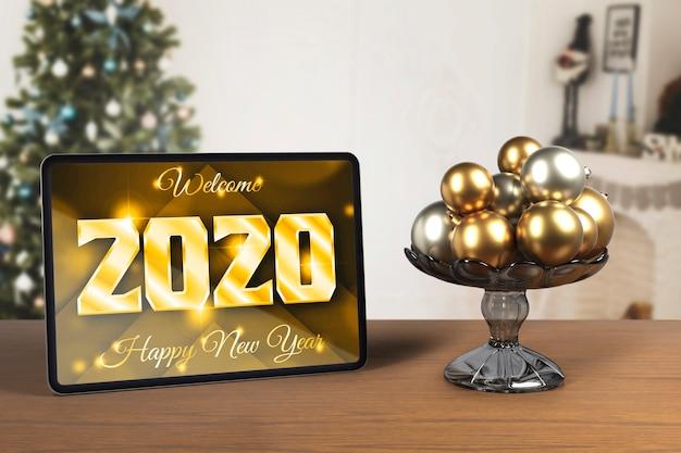 Tableta junto a la bandeja con globos para año nuevo