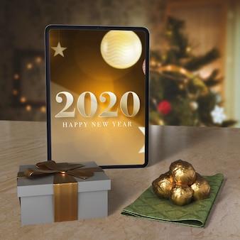 Tableta con mensaje de deseo de año nuevo en la mesa