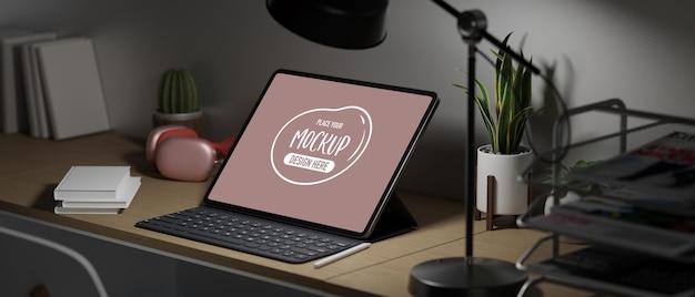 Tableta de pantalla vacía con teclado, auriculares rosa, libros, planta y decoración en la oficina en casa con poca luz