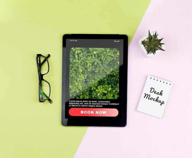 Tableta con planta y cuaderno en escritorio