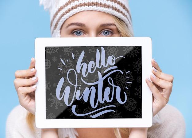 Tableta de primer plano con hola maqueta de invierno