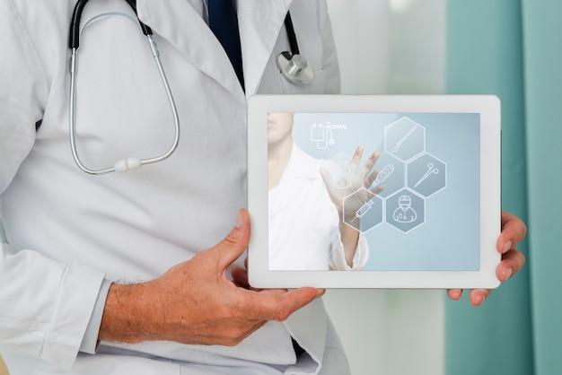 Tableta de primer plano sostenida por un médico