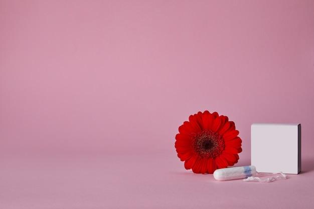 Tamponi mestruali e fiore rosso isolati sulla tavola rosa, vista superiore. copia spazio