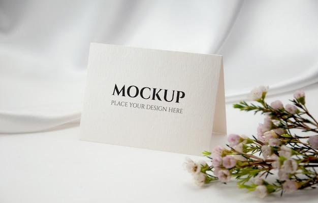 Tarjeta en blanco doblada con flor de cera