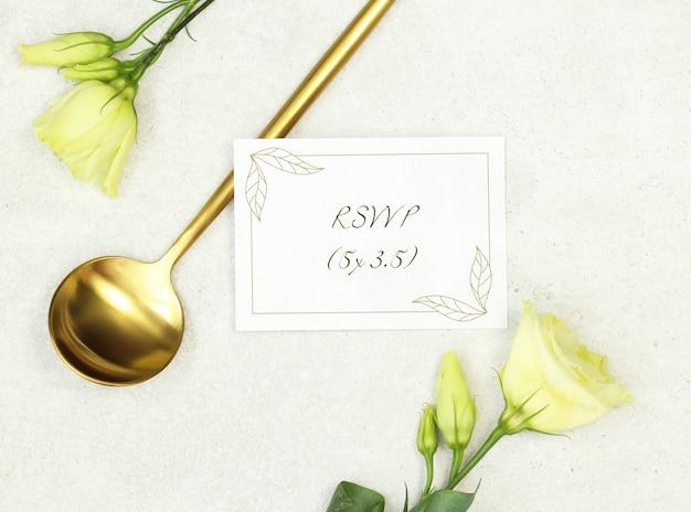 Tarjeta de boda de la maqueta con la cuchara de oro sobre fondo gris