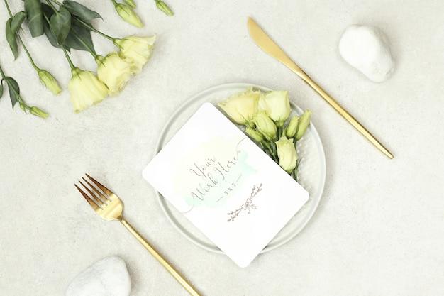 Tarjeta de boda de maqueta con flores y cubiertos de oro